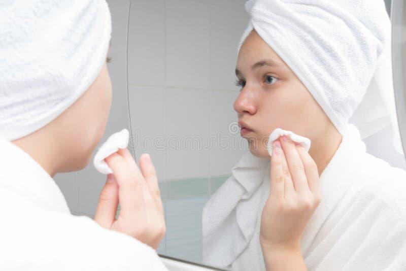 Het tienermeisje veegt haar gezicht met acne in de ochtend af, die zich voor een spiegel bevinden royalty-vrije stock afbeeldingen