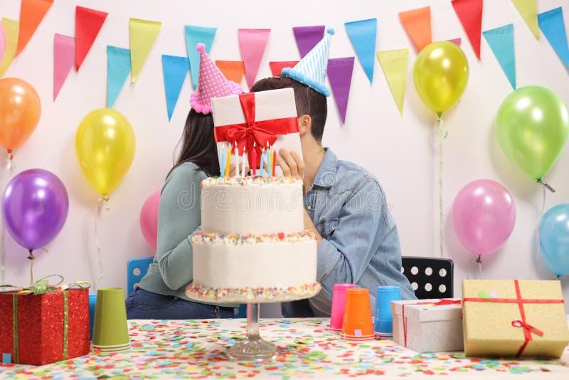Het tienerpaar kussen achter een heden stock afbeeldingen