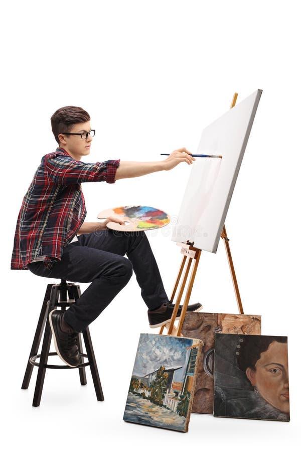 Het tienerschilder schilderen op een canvas met een penseel stock afbeelding