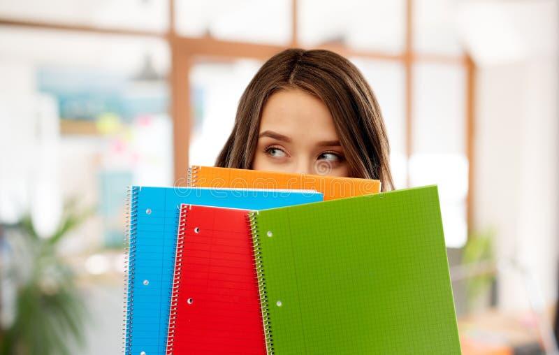 Het tienerstudentenmeisje verbergen achter notitieboekjes stock fotografie