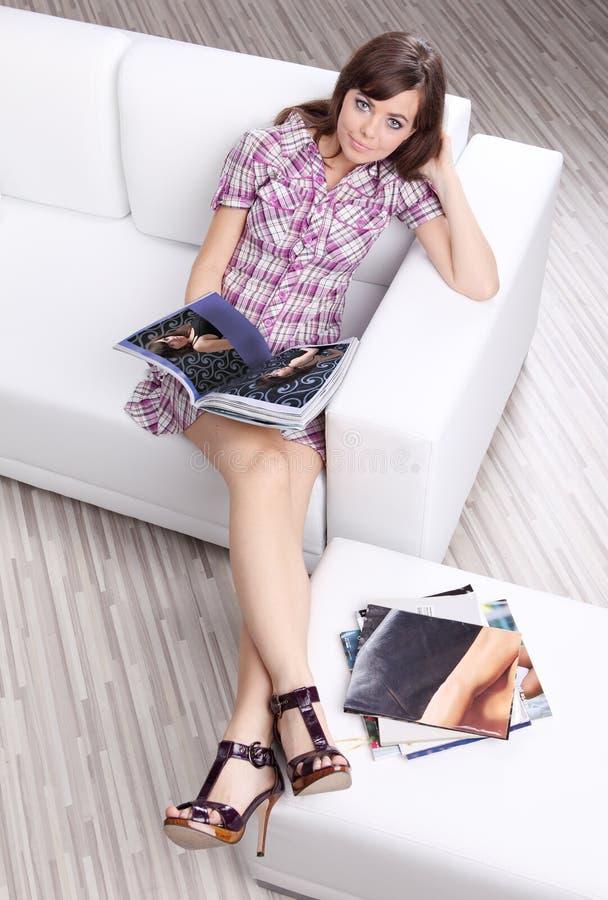Het tijdschrift van de de lezingsmanier van de vrouw op bank stock foto