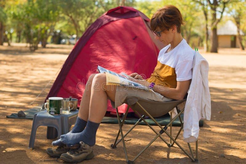 Het tijdschrift van de vrouwenlezing terwijl het ontspannen in het kamperen plaats Tent, stoelen en het kamperen toestellen Openl stock afbeelding