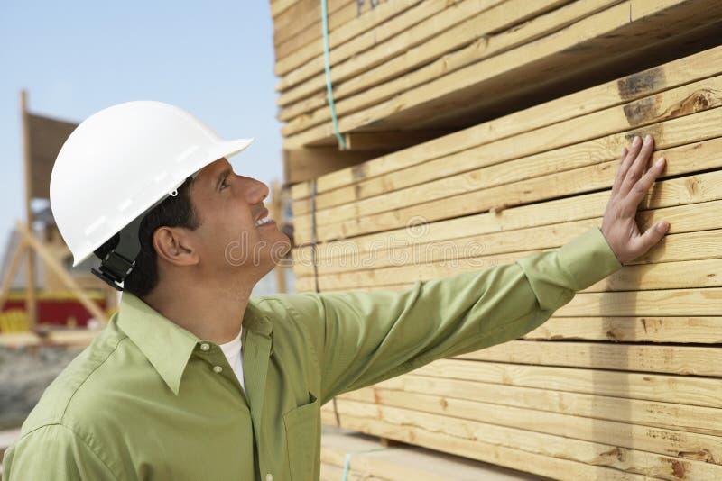 Het Timmerhout van bouwvakkerin hardhat inspecting stock foto