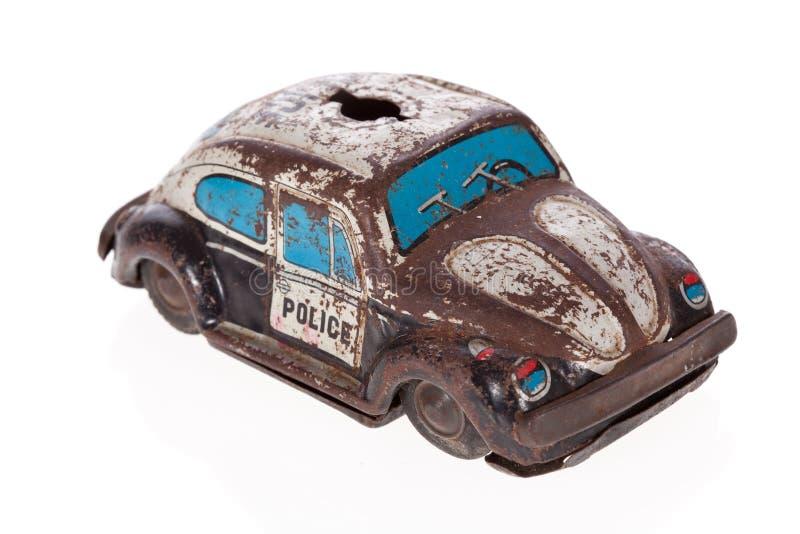 Het tinstuk speelgoed van de politiewagen dat op wit wordt geïsoleerdk stock foto's