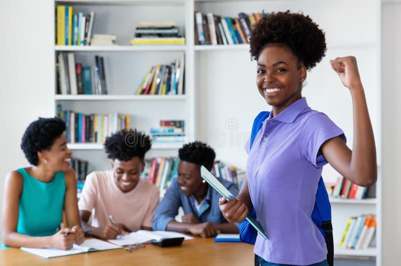 Het toejuichen van Afrikaanse Amerikaanse vrouwelijke jonge volwassene met studenten en leraar royalty-vrije stock afbeeldingen