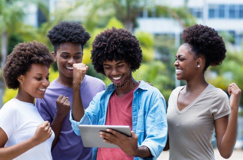 Het toejuichen van groep Afrikaanse Amerikaanse universitaire studenten met digitale tablet stock foto's