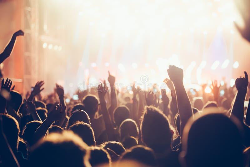 Het toejuichen van menigte met dient lucht bij muziekfestival in stock fotografie