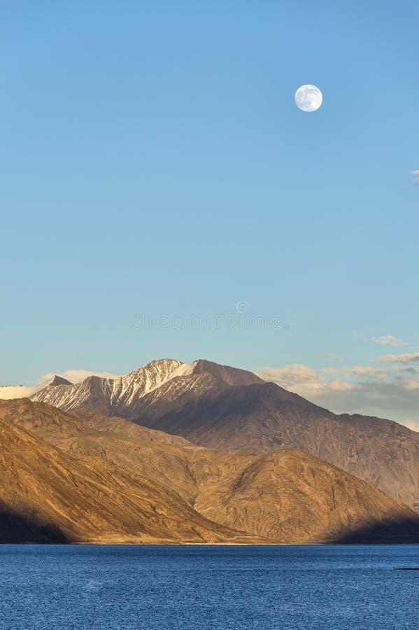 Het toenemen maan over bergmeer stock afbeelding