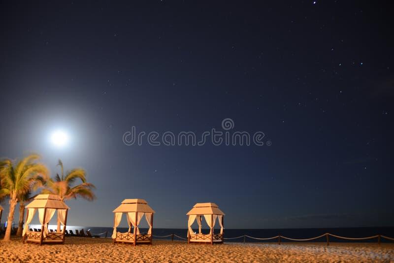 Het toenemen maan over vreedzaam oceaanstrand stock foto