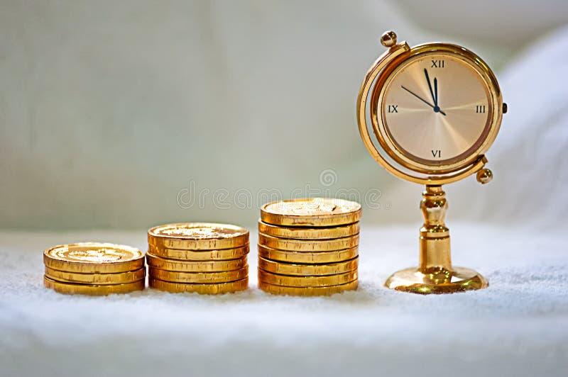 Het toenemen stapel van gouden muntstukken met een klok stock fotografie