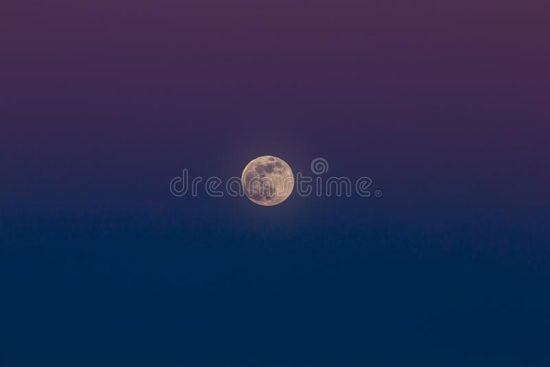 Het toenemen van de volle maan Zonsondergangtijd in de schemeringhemel stock foto's