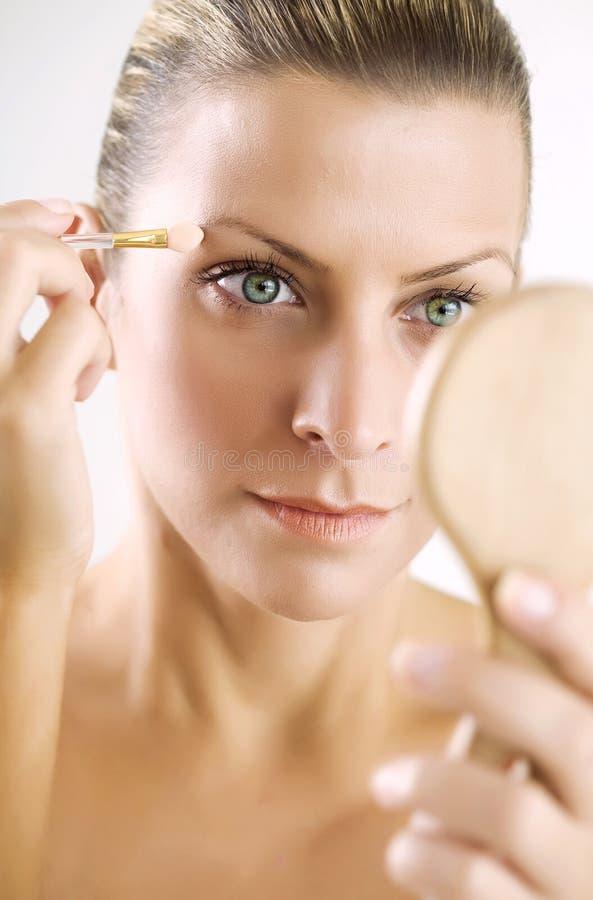 Het toepassen van make-up stock afbeeldingen