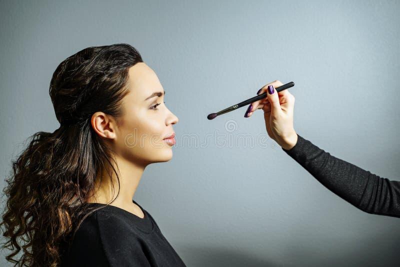 Het toepassen van make-up Portret van een mooie jonge vrouw op een grijze achtergrond royalty-vrije stock fotografie