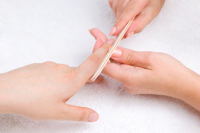 Het toepassen van manicure met spijker-dossier royalty-vrije stock afbeelding