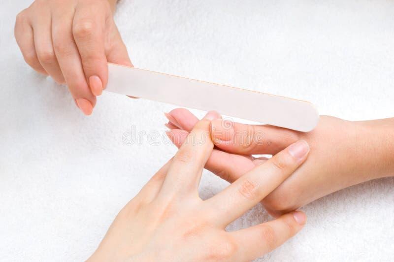 Het toepassen van manicure met spijker-dossier royalty-vrije stock foto's