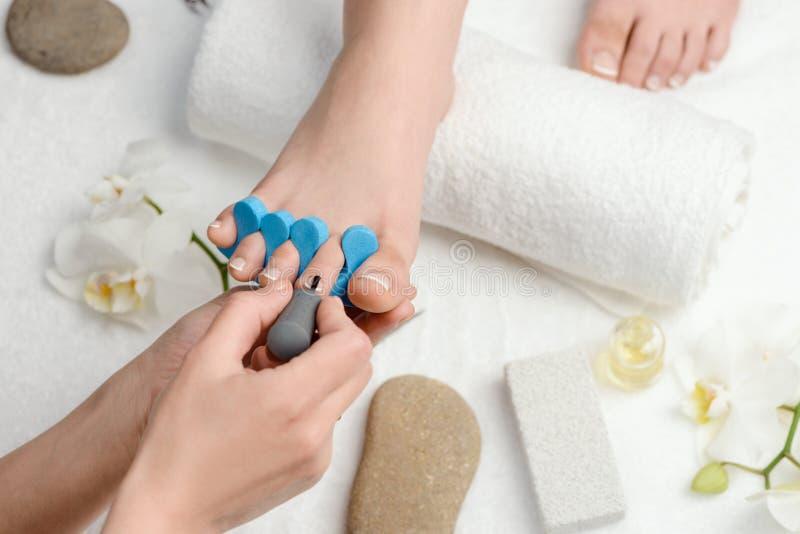 Het toepassen van poetsmiddel op teenspijkers stock foto