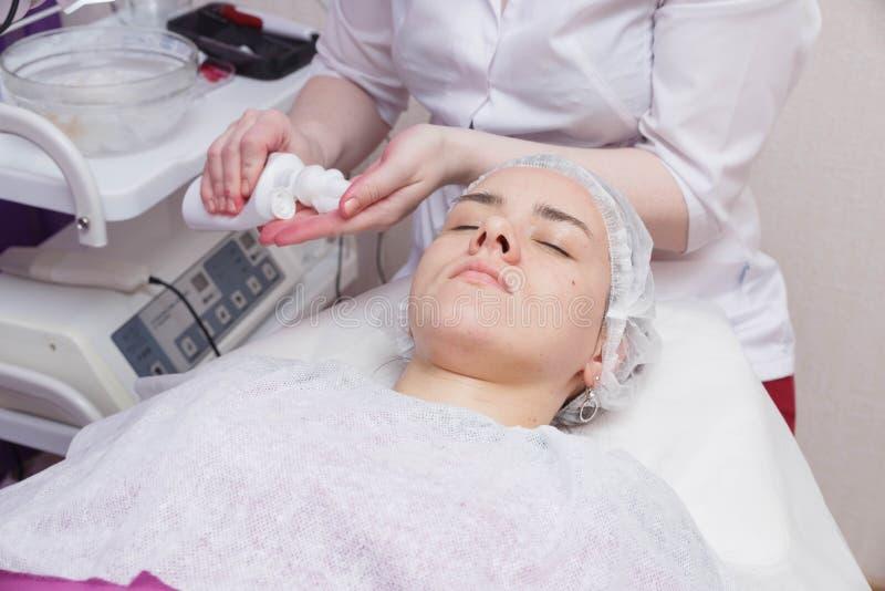 Het toepassen van schuim op het gezicht van het meisje vóór de mesotherapy procedure stock afbeeldingen