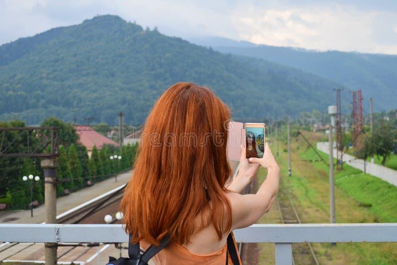 Het toeristenmeisje met rood haar neemt selfie op de brug over het station in een bergstad royalty-vrije stock afbeeldingen