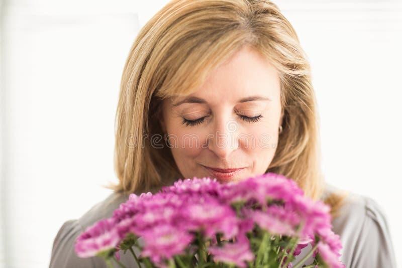 Het toevallige onderneemster ruiken bij bloemen stock foto