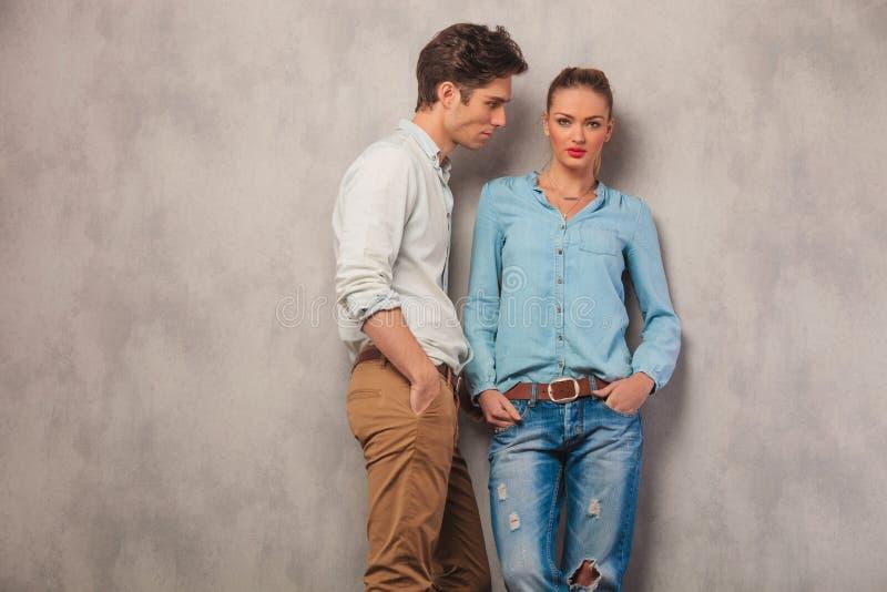 Het toevallige paar stelt op studioachtergrond met indient zakken royalty-vrije stock afbeelding