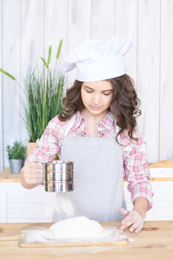 Het toevoegen van Bloem Testvoorbereiding Meisje in keuken Weinig kok stock foto's