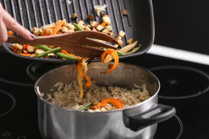 Het toevoegen van geroosterde groenten aan gekookte rijst in steelpan royalty-vrije stock afbeelding