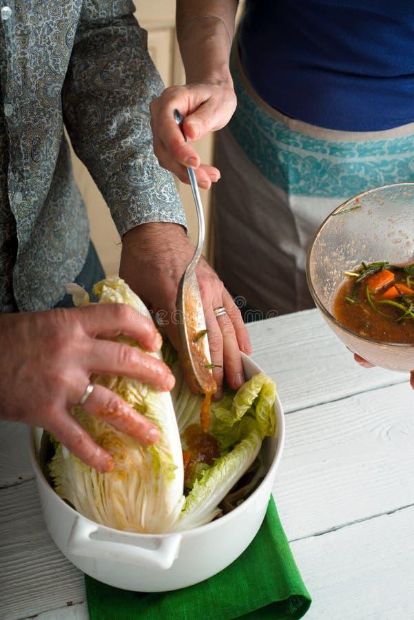 Het toevoegen van marinade aan de Chinese kool stock afbeelding
