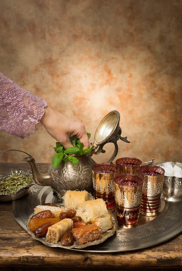 Het toevoegen van munt aan Marokkaanse thee stock foto