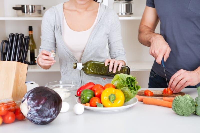 Het toevoegen van olijfolie terwijl het koken van salade stock fotografie