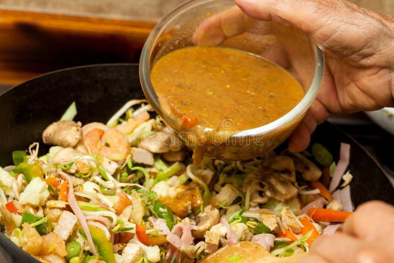 Het toevoegen van saus aan de groenten en het vlees in een wok stock foto's