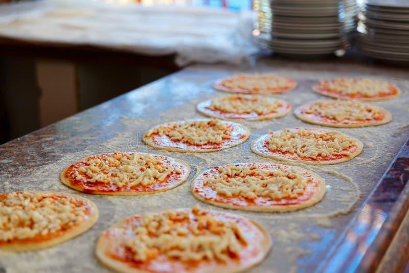 Het toevoegen van Tomatensaus aan Pizzabasis stock afbeeldingen