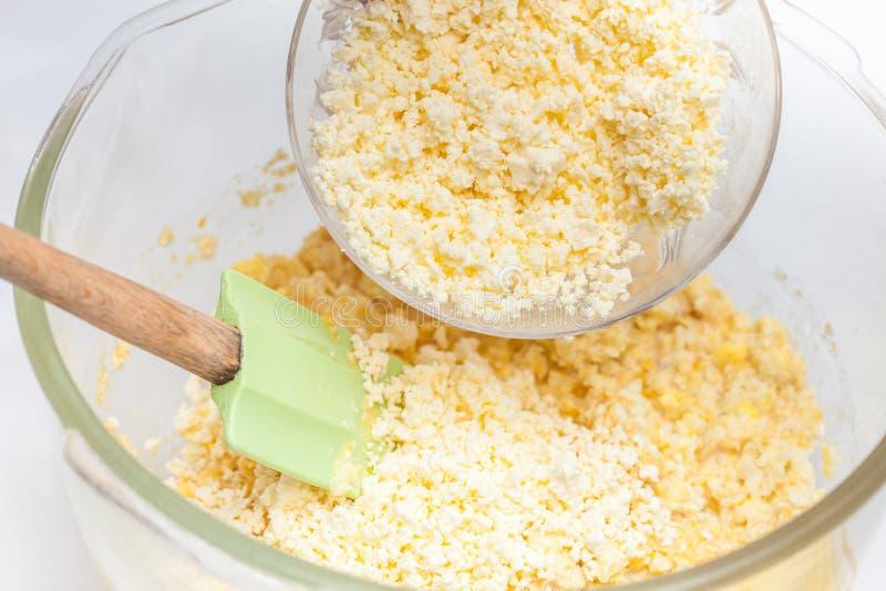 Het toevoegen van verscheurde kaas om suikermaïsbrood voor te bereiden stock fotografie