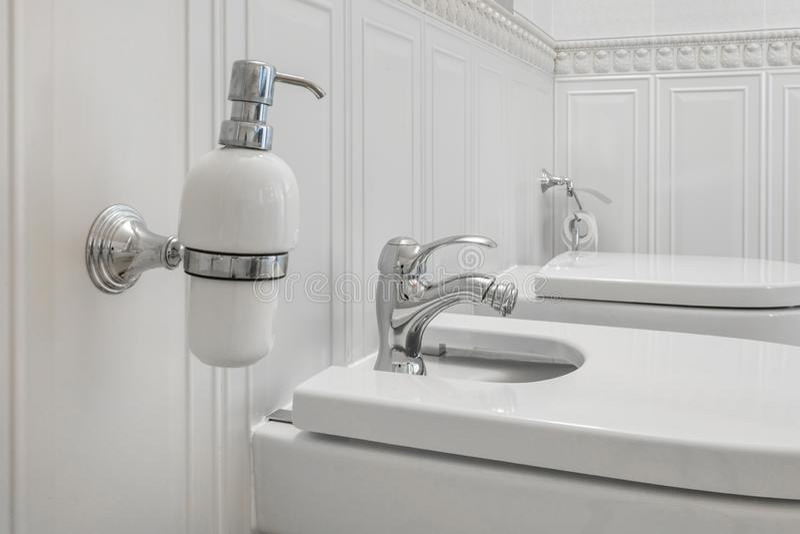 Het toilet en het detail van een bidet van de hoekdouche met zeep en shampooautomaten op muur zetten douchegehechtheid op stock afbeelding
