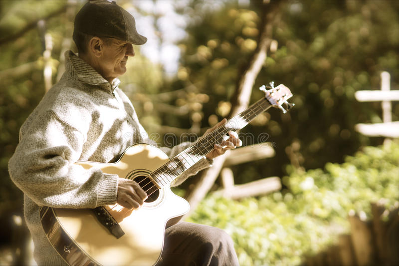Het tokkelen van gitaar in middaglicht stock afbeeldingen