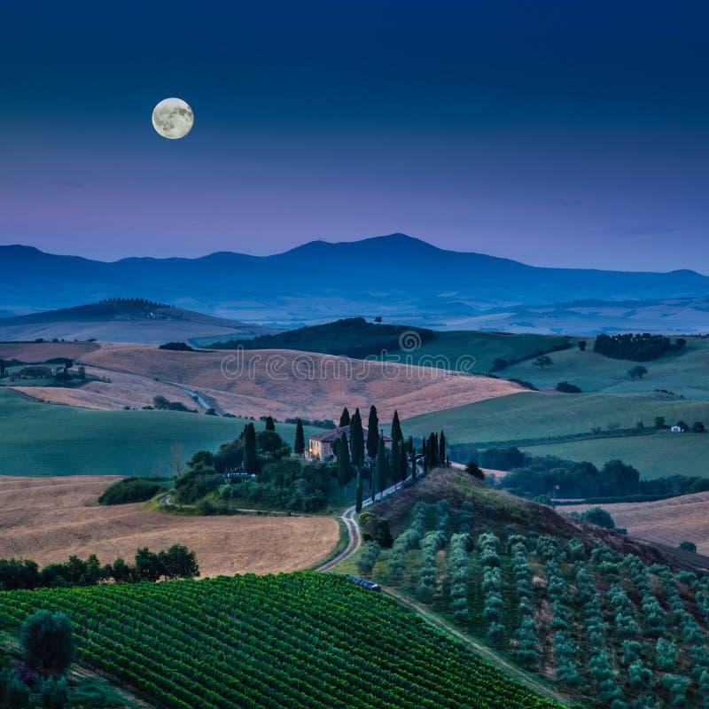Het toneellandschap van Toscanië met rollende heuvels onder volle maan stock fotografie