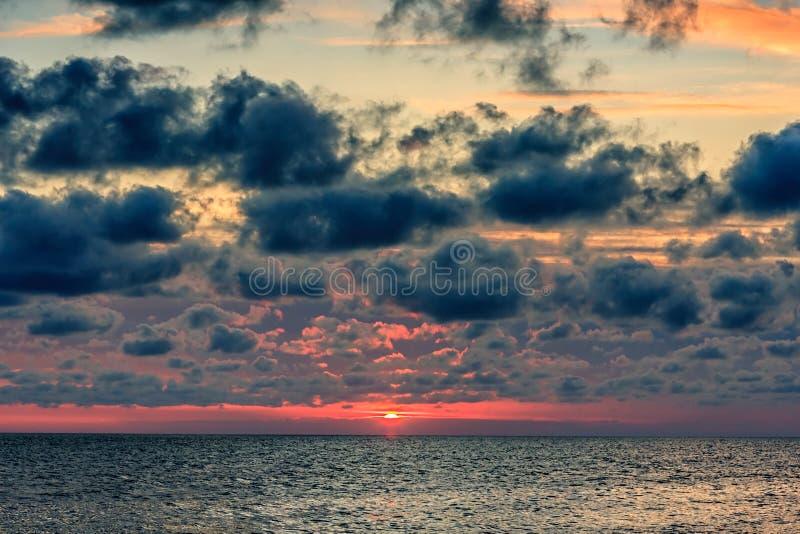 Het toneelzeegezicht van de zonsondergangzwarte zee met zwarte wolken over horizon royalty-vrije stock fotografie