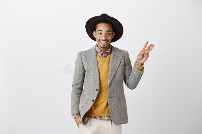 Het tonen van drie manieren of keuzen Studio van tevreden succesvolle Afrikaanse vriend in modieuze hoed en grijs jasje wordt ges stock foto's