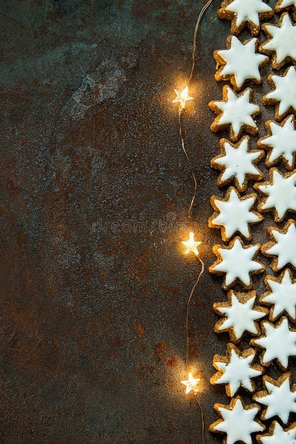 Het traditionele Duitse Huis van Kerstmiskoekjes bakte Verglaasde Kaneelsterren met Noten het Fonkelen Garland Lights op Rusty Da stock foto's