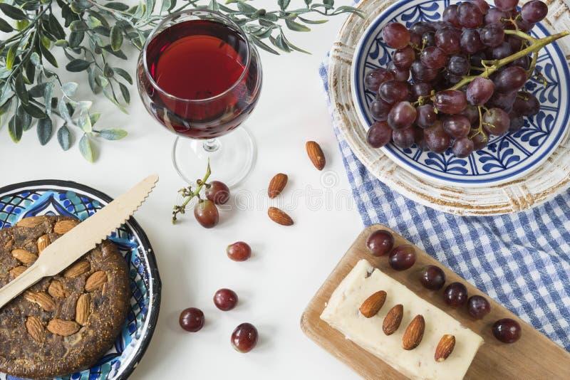 Het traditionele Griekse voedsel, vlakke snack, legt met fig.brood, rode wijn, druiven stock fotografie