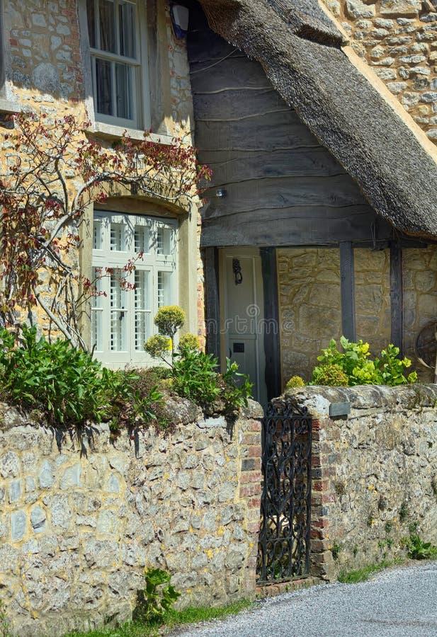 Het traditionele steenplattelandshuisje met met stro bedekt dak royalty-vrije stock afbeeldingen