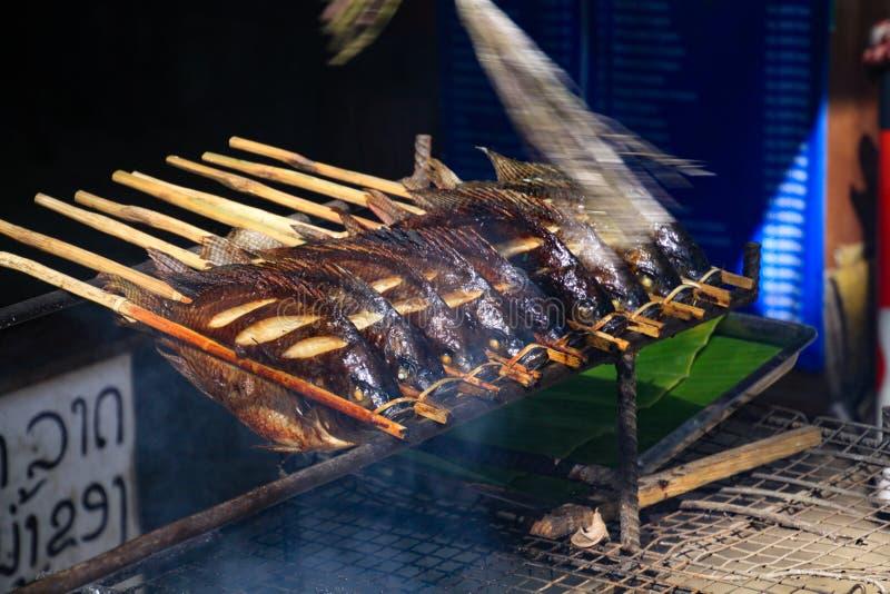 Het traditionele voedsel van de barbecuestraat met vissen op een rij op houten vleespennen bij de houtskoolgrill - Vang Vieng, La stock afbeelding