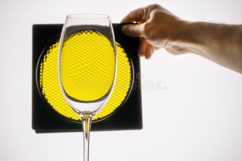 het transparante glas houdt hand op een achtergrond van gele honingraat stock fotografie