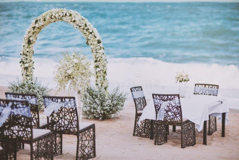 Het trefpunt die van het strandhuwelijk met bloemdecoratie plaatsen op boog, panoramische oceaanmening royalty-vrije stock foto's