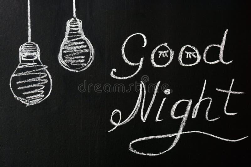 Het trekken met krijt op een zwarte achtergrond die - u een Goede nacht met de geschilderde gloeilampen wensen royalty-vrije stock afbeelding
