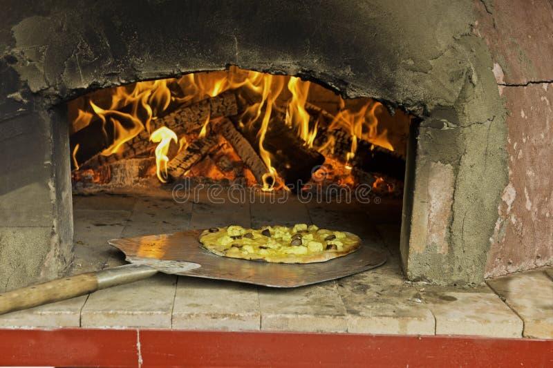 Het trekken van een pizzarecht uit de oven royalty-vrije stock foto