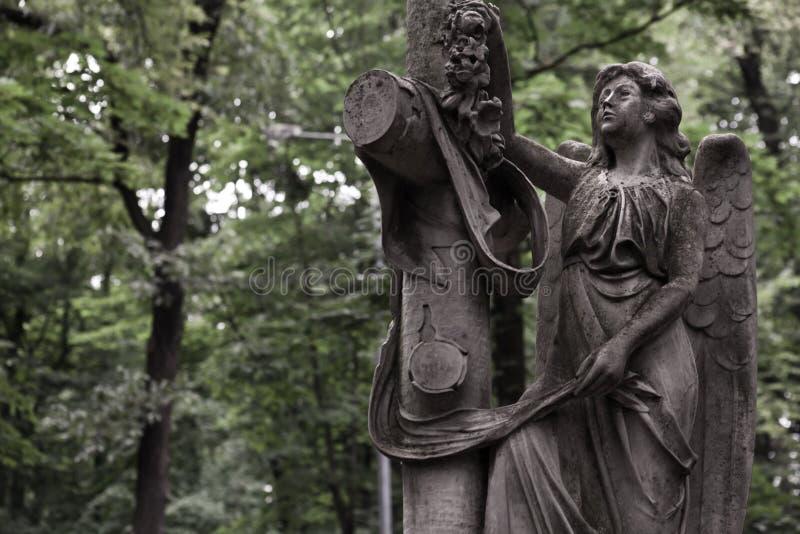 Het treuren van engel tegen een achtergrond van donkergroen gebladerte royalty-vrije stock afbeeldingen