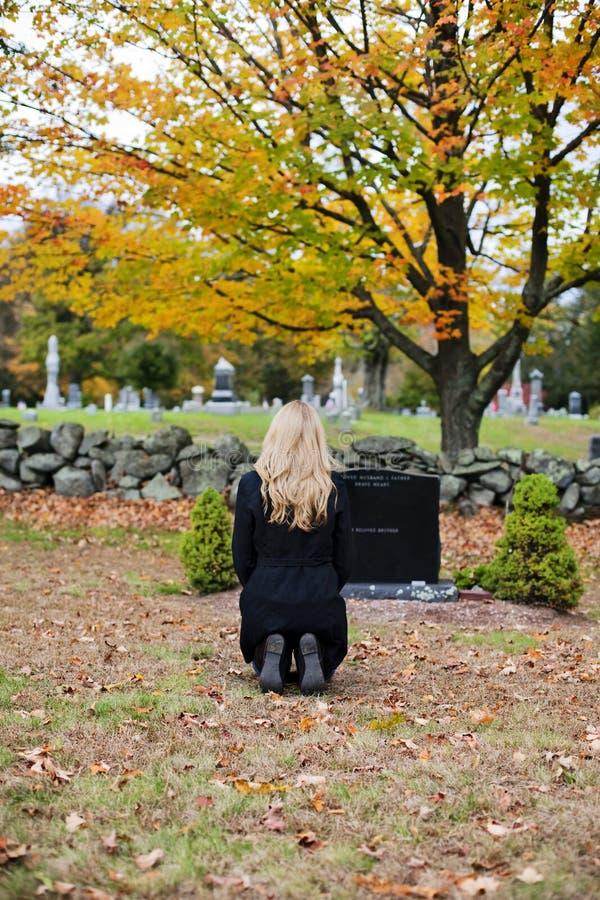 Het treuren van vrouw in begraafplaats stock afbeelding