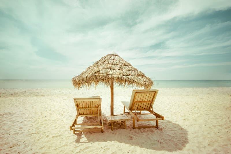 Het tropische strand met met stro bedekt paraplu en stoelen voor ontspanning royalty-vrije stock foto