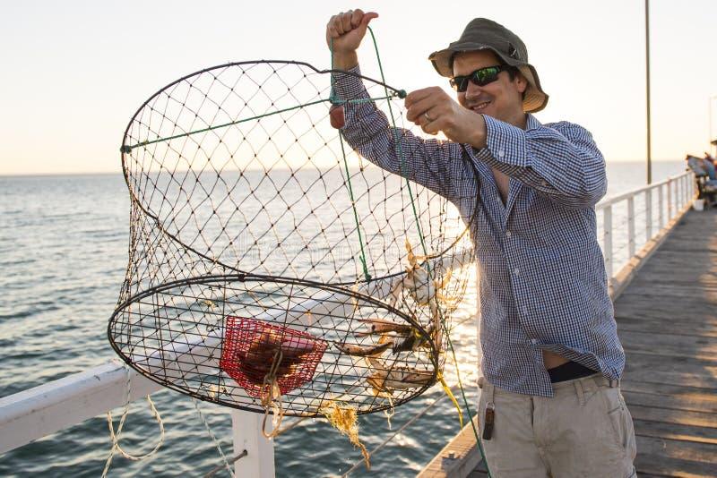 Het trotse aantrekkelijke visser tonen vissen en de krabbenmand netto vangst glimlachend op zee dokzonsondergang bij de mens die  royalty-vrije stock afbeeldingen