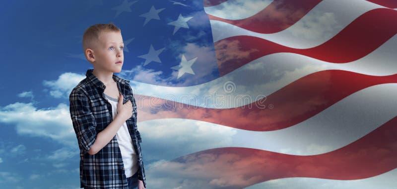 Het trotse Patriottische jonge geitje bekijkt Amerikaanse vlag stock foto's